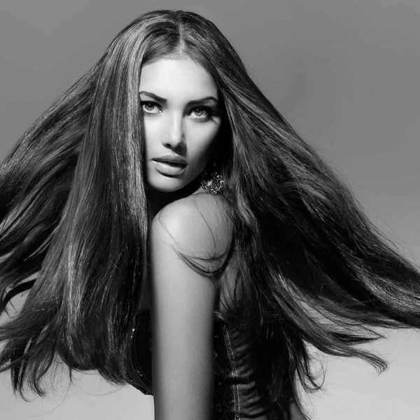 woman-twirlling-long-flowing-hair-in-black-and-white